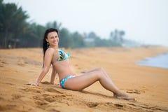 Mooie vrouw die op het zand op het strand in de zomer liggen Het geluk onbezorgde blije vrouw van de de zomervakantie royalty-vrije stock foto