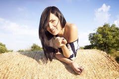 Mooie vrouw die op hooi leggen stock foto