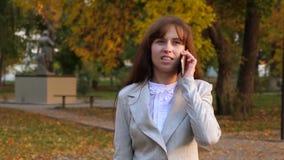 Mooie vrouw die op mobiele telefoon, gelukkig meisje spreken die door de herfst het Park en het glimlachen lopen stock video