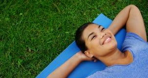 Mooie vrouw die op oefeningsmat in tuin 4k liggen stock videobeelden