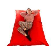 Mooie vrouw die op rode vierkante gevormde beanbag geïsoleerde bank liggen Royalty-vrije Stock Foto