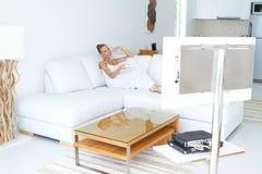Mooie vrouw die op TV in huis let binnen Stock Afbeelding
