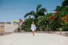Mooie vrouw die op witte kleding alleen bij de muren lopen die de koloniale stad van Cartagena DE Indias omringen stock afbeeldingen