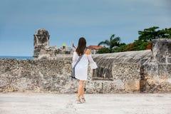 Mooie vrouw die op witte kleding alleen bij de muren lopen die de koloniale stad van Cartagena DE Indias omringen stock foto's