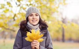 Mooie vrouw die in park loopt Meisje over seizoengebonden de herfstachtergrond Stock Fotografie