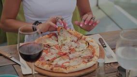 Mooie vrouw die pizza op het terras van een restaurant eten stock videobeelden