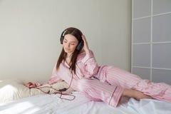 Mooie vrouw die in Pyjama's aan muziek met hoofdtelefoons in bedslaapkamers luisteren royalty-vrije stock afbeelding