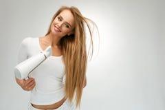 Mooie Vrouw die Recht Haar drogen die Droger met behulp van hairdressing royalty-vrije stock foto