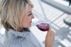 Mooie vrouw die rode wijn in portiek ruiken stock fotografie