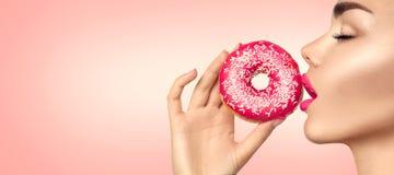 Mooie vrouw die roze doughnut eet stock afbeelding