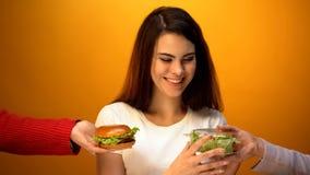 Mooie vrouw die salade in plaats van hamburger, gezondheidszorg versus ongezonde kost kiezen royalty-vrije stock fotografie