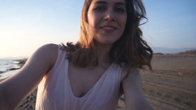Mooie vrouw die selfie gebruikend telefoon op strand bij en zonsondergang die genietend van aard en levensstijl glimlachen spinne