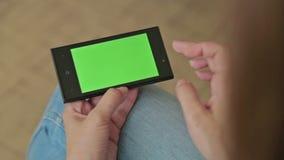 Mooie vrouw die slimme telefoon met groene het schermvertoning houden en wat betreft stock video