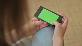 Mooie vrouw die slimme telefoon met het groene het schermvertoning en scrollen houden stock footage