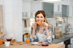 Mooie vrouw die smakelijk geroosterd brood met jam eten royalty-vrije stock afbeelding