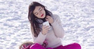 Mooie vrouw die smartphone op sneeuw gebruiken stock video