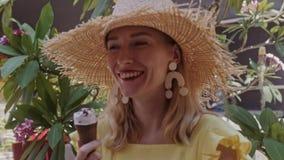 Mooie vrouw die in strohoed roomijs in openlucht Straat eten De zomerportret stock videobeelden