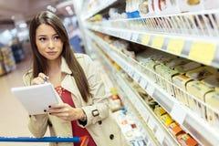 Mooie vrouw die in supermarkt winkelen Stock Foto