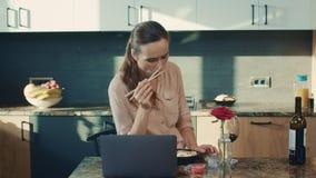 Mooie vrouw die sushi eten bij luxehuis Verstoorde vrouw het letten op laptop stock videobeelden