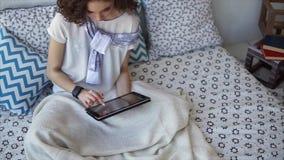 Mooie vrouw die tabletcomputer het online winkelen gebruiken thuis zittend op bed stock video