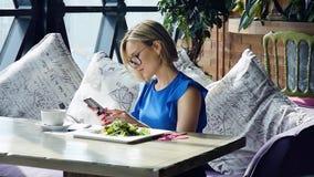 Mooie vrouw die tijdens lunch rusten, die in een koffie zitten Bedrijfs lunch Langzame Motie stock footage