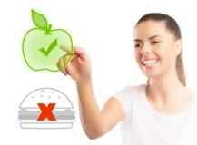 Mooie vrouw die tussen gezond en ongezond voedsel kiezen stock foto's