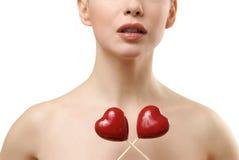 Mooie vrouw die twee rode harten gekruist houdt. Stock Foto's