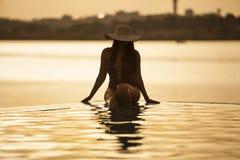 Mooie vrouw die van de pool genieten stock foto