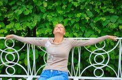 Mooie vrouw die van de zon op een bank geniet royalty-vrije stock fotografie