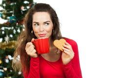 Mooie vrouw die van hete drank en peperkoek genieten royalty-vrije stock afbeelding