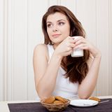 Mooie vrouw die van thee en koekjes geniet Stock Afbeelding