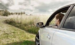 Mooie vrouw die van venster van auto kijkt Royalty-vrije Stock Afbeeldingen