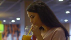 Mooie vrouw die vers sap drinken, die in camera, vitaminen en energie glimlachen stock videobeelden