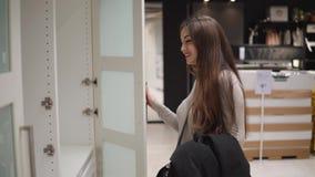 Mooie vrouw die vinden nieuw meubilair stock footage