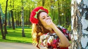 Mooie vrouw die in volks gestileerd kostuum uit van berk met lensgloed gluren stock videobeelden