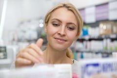 Mooie vrouw die voor geneeskunde winkelen stock fotografie