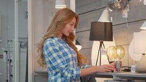 Mooie vrouw die voor verlichting voor haar flat bij meubilairopslag winkelen stock video