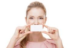 Mooie vrouw die witte kaart houden bij voorzijde van haar lippen Geïsoleerde stock afbeeldingen