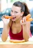 Mooie vrouw die wortelen thuis eten royalty-vrije stock fotografie