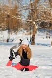 Mooie vrouw die yoga in openlucht in de sneeuw doen stock foto's