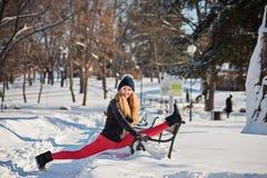 Mooie vrouw die yoga in openlucht in de sneeuw doen stock fotografie