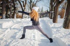 Mooie vrouw die yoga in openlucht in de sneeuw doen royalty-vrije stock foto