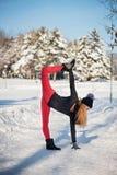 Mooie vrouw die yoga in openlucht in de sneeuw doen stock foto