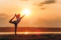 Mooie vrouw die yoga in openlucht doen bij zonsondergang Royalty-vrije Stock Foto's