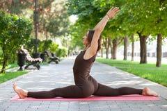 Mooie vrouw die yogaoefeningen in het park doen stock afbeeldingen