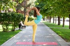 Mooie vrouw die yogaoefeningen in het park doen stock afbeelding