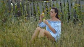 Mooie Vrouw die Zeepbels laten die op het Gras dichtbij de Houten Omheining zitten stock video