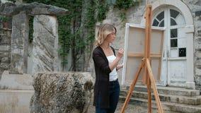 Mooie vrouw die zich bij een schildersezel bevinden en een borstel en een palet houden stock footage