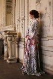 Mooie vrouw die zich in de paleisruimte bevinden royalty-vrije stock afbeelding