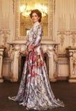 Mooie vrouw die zich in de paleisruimte bevinden Stock Afbeeldingen